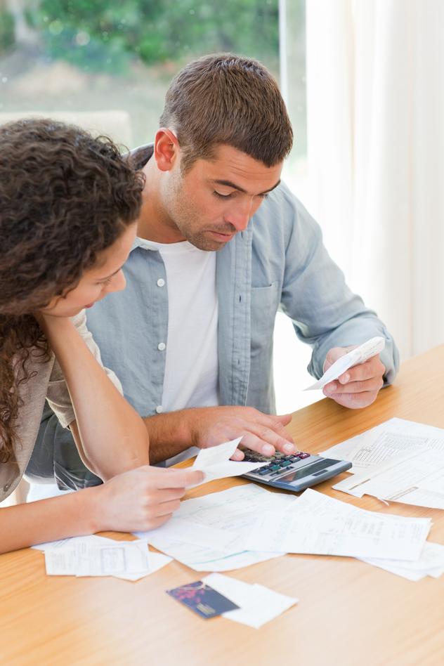 Junges Paar sitzt zu Hause und überprüft Rechnungen